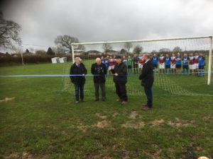 Picture of the opening ceremony showing the Chairman of the Parish Council and members of the Football Club cutting the ribbon